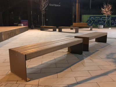 Elements 2.4m benches with medium side-to-side timber slats and powder coated corten-effect plate ends