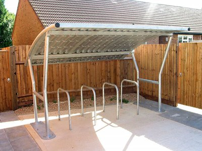 ACA800F Academy galvanised steel cycle shelter with corrugated roof with four College cycle stands, Haynes