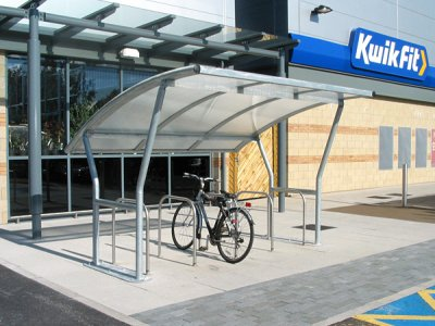 ACA800TP Academy galvanised steel cycle shelter with polycarbonate roof, shown with College cycle stands, York