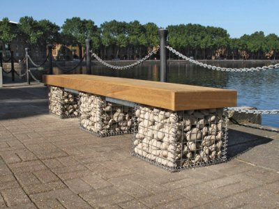 Elements 2.4m bench with medium slats and timber fascias. Gabions filled with Scottish beach cobbles
