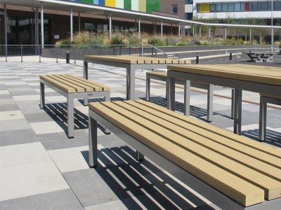 Parallel picnic benches and tables, both with wood plastic composite slats