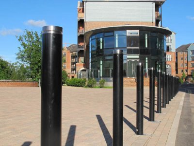 LNB 100 Linx Kenton satin polished cap bollards installed within FI 115 large sockets.