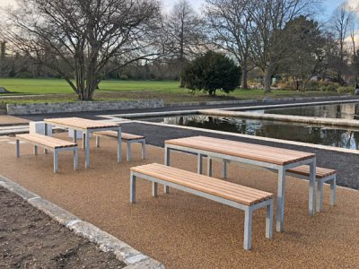 Parallel picnic benches and tables, both with iroko timber slats